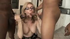 Buxom blonde milf Nina Hartley has two black cocks exploring her holes