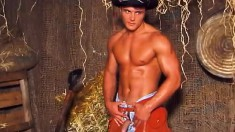 Handsome young cowboy displays his muscled body and strokes his cock