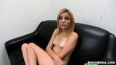 Sitting on the sofa, she plays with her cunt until a big rod arrives and she sucks it