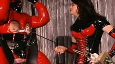 Mistresses in latex get their fat slave in latex to sit on a Sybian